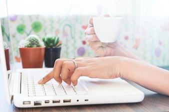 Femme utilisant un ordinateur portable et boire du café à la maison, concept de travail à la maison