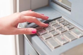 Femme utilisant une machine bancaire. Fermer