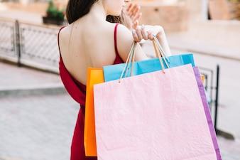 Femmes avec des sacs en papier derrière son dos