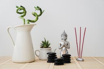 Figure de Bouddha avec des pierres noires, de l'encens et de la végétation