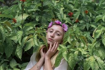 Fille avec les mains sur le visage et entouré de plantes