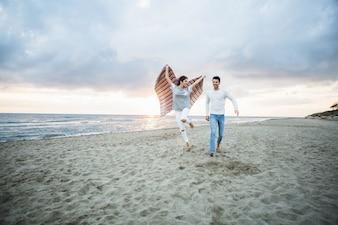Fille courir sur la plage avec une couverture et son petit ami à côté de