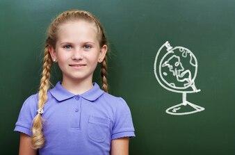fille intelligente avec un globe sur le tableau noir