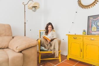 Fille lisant un livre assis sur une chaise