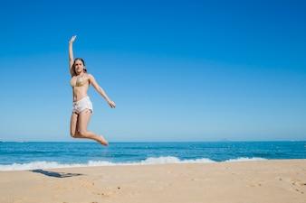 Fille sautant à la plage