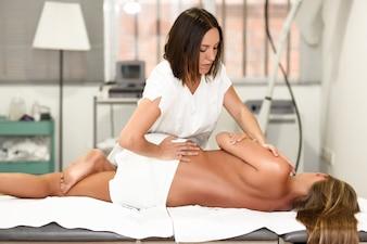 Fisiothérapeute professionnelle donnant massage aux épaules à la femme blonde