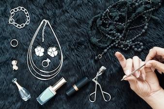 Flat lay closeup shot d'une femme ongles manucure par elle-même. Femme obtient une manucure aux ongles avec ses objets de beauté sur fond de laine noire
