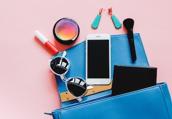 Flat lay of blue leather leather bag open out with cosmetics, accessories, wallet and smartphone on pink background with copy space