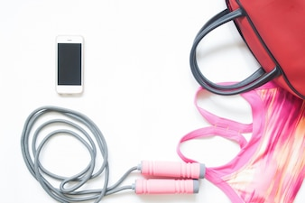 Flat lay of sport and fitness equipment with smartphone isolated on white background