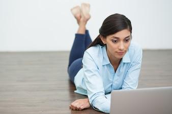 Focused Femme couchée sur le plancher et travailler sur un ordinateur portable