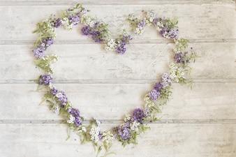 Fond en bois avec cadre floral en forme de cœur