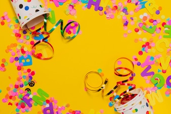 Fond jaune avec des lunettes et la décoration de fête