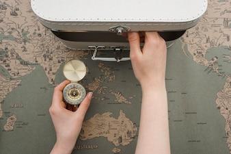 Fond Voyage avec les mains tenant une boussole et d'ouvrir une valise
