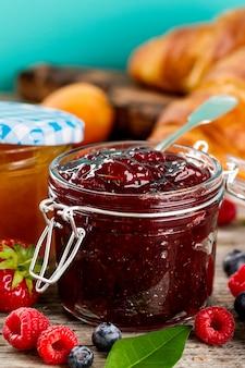 Fruits savoureux fraises fraises fraises au pot de verre avec des fruits sur une table en bois. Fermer.