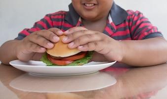 Garçon asiatique mange un hamburger, la malbouffe malsaine pour les enfants