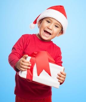 Garçon Enthousiaste tenant son cadeau avec les deux mains