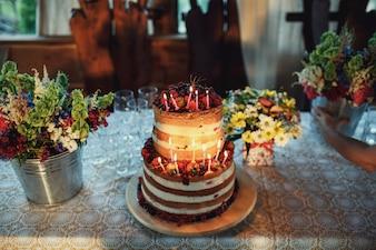 Gâteau fatigué en crème blanche et baies aux bougies allumées