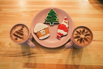 Gingerbreads with Christmas design se trouvent sur une assiette rose entre des tasses avec du café