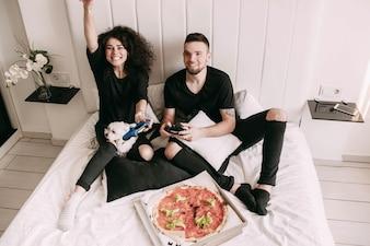 Girl gagne le jeu avec l'homme sur PS sur le lit