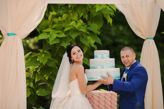 Grooms de levage le gâteau de mariage
