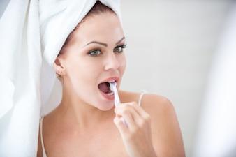 Gros plan de femme concentrée brossant les dents