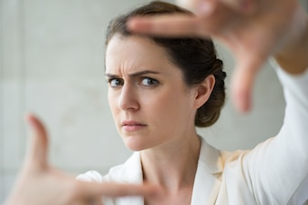 Gros plan de Frowning Woman Making Gesture Frame