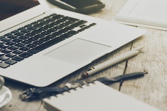 Gros plan de l'espace de travail avec un ordinateur portable créatif moderne, une tasse de café et des crayons. Horizontal avec espace de copie.