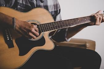 Gros plan de la main de la barbe hipster jouant de la guitare.