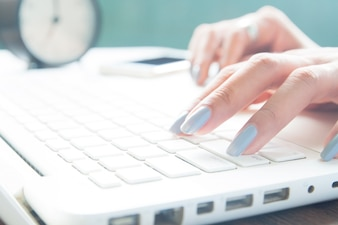 Gros plan des doigts féminins à l'aide d'un ordinateur portable, d'un travailleur et d'un concept de magasinage en ligne