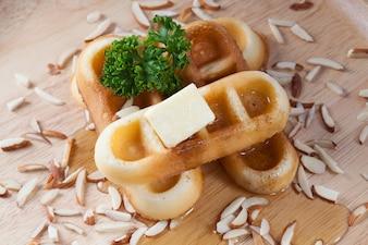 Gros plan, versez le miel du haut des gaufres et des noix qui ont du persil et du fromage au dessus des gaufres sur une assiette en bois pour le petit-déjeuner.