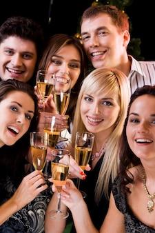 Groupe d'amis tenant des lunettes de champagne