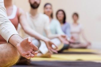 Groupe de gens qui font la méditation sur le tapis d'exercice