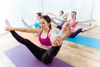 Groupe de personnes qui pratiquent le yoga à la maison. Upavistha konasana pose.