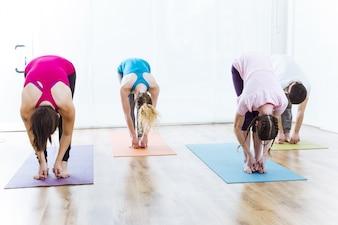 Groupe de personnes qui pratiquent le yoga à la maison. Uttanasana pose.
