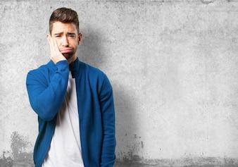 Guy dans une veste bleue avec toothache