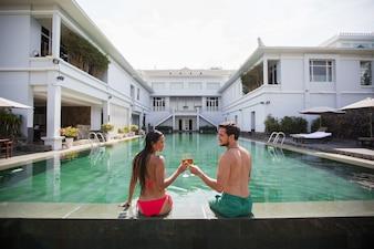 Happy Couple Drinking Champagne au bord de la piscine