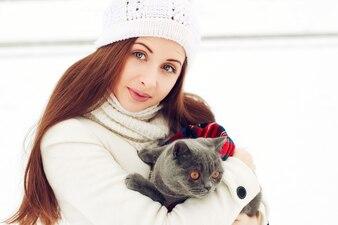 Happy femme portant un chapeau de laine et étreindre son chat