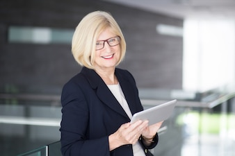 Happy Senior Business Lady Using Tablet dans Lobby