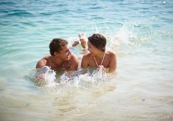 Heureux couple de jouer dans l'eau