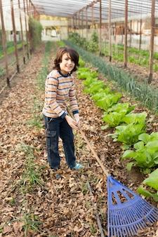 Heureux enfant essuyant les feuilles sèches avec un râteau