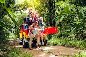 Heureux jeunes voyageurs asiatiques avec 4WD conduisent la voiture hors route en forêt, jeune couple à la recherche de directions sur la carte et deux autres apprécient sur 4WD drive car. Jeune femme asiatique mixte et homme.