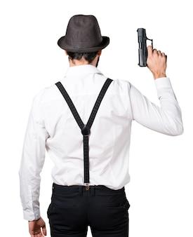 Hipster homme à la barbe avec un pistolet