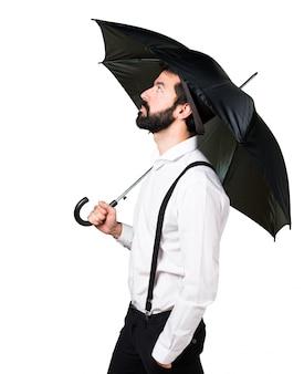 Hipster homme à la barbe tenant un parapluie