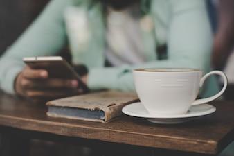 Hipster, jeune homme beau, utilisant son téléphone intelligent, assis au comptoir de la barre au fond du café.
