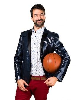 Homme avec une veste tenant un ballon de panier