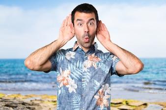Homme beau avec un pantalon de fleur écoutant quelque chose à la plage