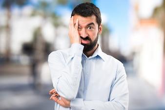 Homme bel homme fatigué avec de la barbe sur un fond non focalisé