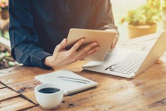 Homme d'affaires asiatique utilisant une tablette et un ordinateur portable sur table dans un café avec un filtre tonique vintage.
