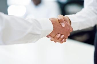 Homme d'affaires caucasien serrant la main avec une femme d'affaires en plein