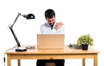 Homme d'affaires dans son bureau avec douleur à l'épaule